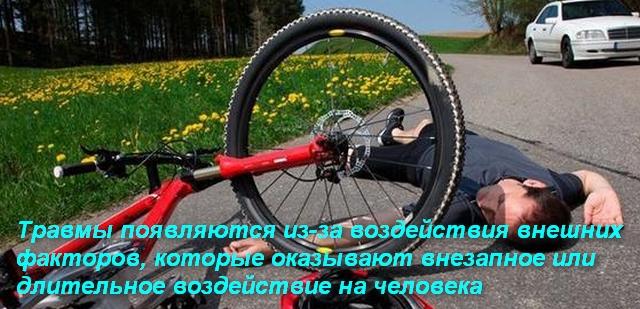 человек упал с велосипеда и лежит на дороге