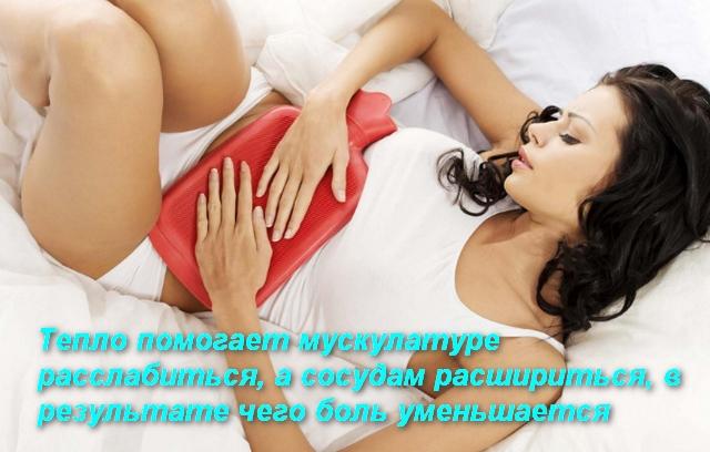 женщина держит грелку на животе