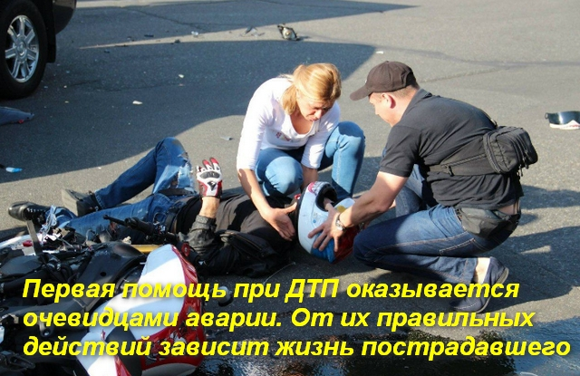 женщина и мужчина помогают лежащему мотоциклисту